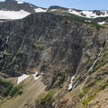 Swiftcurrent Glacier, the Waterfall Wall, and the trail seen from high along the exposed traverse.- Swiftcurrent Pass Trail