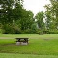 Open campsites with tables and fire pits.- Crown Point Campground