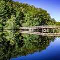 Take the footbridge over Byrd Lake to explore the park's trails.- Cumberland Mountain State Park