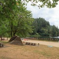 Large grassy picnic area against the sandy beach.- Loon Lake Recreation Site