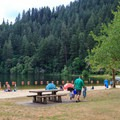 Large grassy picnic area against a sandy beach.- Loon Lake Recreation Site