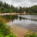 View of the sandy beach from the trail to the falls.- Loon Lake Recreation Site
