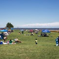 Families setup for a day of relaxing in an open field.- Sandy Point State Park