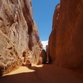 A narrow section of trail between two rock structures.- Sand Dune Arch