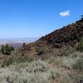 The trail wraps around the first view of the fire lookout.- Schonchin Butte