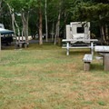 An RV site with electric and water hookups.- Chéticamp Campground