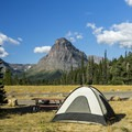 Sinopah Mountain rises across the lake.- Two Medicine Campground