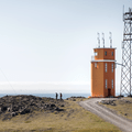 A radio tower stands next to the lighthouse.- Hvalnes Lighthouse