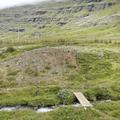 A wooden bridge crossing over a stream.- Neðri-Stafur and Seyðisfjörður