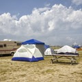 A campsite featuring just a small tent.- Delaware Seashore State Park Campground