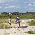 A couple reading an informational sign.- Assateague Island National Seashore