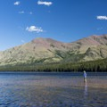 The area around the west boat dock is great for wading or swimming.- Two Medicine Lake Loop Hike