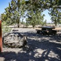 Sites contain picnic tables, fire pits, and grills.- Indian Well Campground