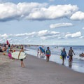 People carry surfboards and walk along the shore.- Assateague Island National Seashore