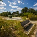 A bench along the trail with a large gun behind.- Fort Miles Historical Area