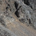 Two hikers cautiously navigate up the most difficult section of the pass featuring very steep and loose rocks.- Paintbrush Canyon to Cascade Canyon Loop