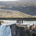 People standing on a rock outcropping.- Goðafoss