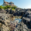 A large rock formation with a private residence sits in the middle of the beach.- Mother's Beach