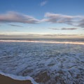 Waves slowly roll onto the shore.- Fenwick Island State Park