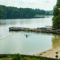 Swimming area with its sandy beach and nearby paddleboat dock.- Unicoi State Park + Lodge
