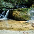 A small waterfall visible from a hiking trail in Keowee Toxaway State Park.- Keowee Toxaway State Park