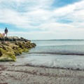 A family climbs the rocky jetty to look at the Scarborough River.- Pine Point Beach