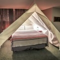 Canopied bed inside the Great Indoors room.- Basecamp Tahoe South