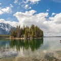 Canoers paddling by Boulder Island in Leigh Lake, with Mount Moran in the background.- String Lake Loop
