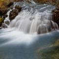 A spot to cross Lake Fork Creek with autumn leaves swirling on the side.- Mystic Falls