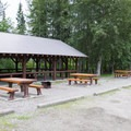 Common picnic shelter and tables near the day use parking area.- Liard River Hot Springs Campground
