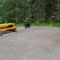 Each site has a picnic table and fire ring with grate.- Liard River Hot Springs Campground