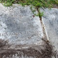 Brushing away dirt to reveal the age of this grave.- Chapel of Ease Ruins