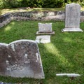 Gravestones surrounded by a low tabby wall.- Chapel of Ease Ruins