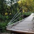 A suspended bridge crossing the creek. Guests are encouraged to stay on marked trails only.- Konza Nature Preserve