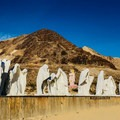 """""""The Last Supper"""" in the foreground with """"Lady Desert: The Venus of Nevada"""" in the middle-ground and a derelict mine puncturing the hill in the background.- Goldwell Open Air Museum"""