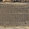 """Eames Demetrios's """"Rhyolite's District of Shadows"""" offers an alternative narrative to Rhyolite's evolution. The ghost town is prominent in the background as you read the plaque.- Goldwell Open Air Museum"""