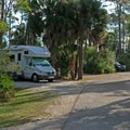 An RV pulled into a campsite.- T. H. Stone Memorial St. Joseph Peninsula State Park Campground