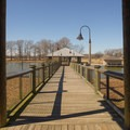 A pier going across a finger of the reservoir. - Poverty Point Reservoir State Park