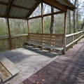 A boardwalk walkway and sitting area at Slidell Trailhead.- Tammany Trace