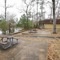 Cabins have outdoor tables and fire pits. - Sam Houston Jones State Park Campground