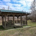 A shaded sitting area sits beside the pond. - White Lake Wetlands Conservation Area Birding + Nature Trail