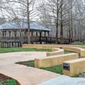 A small amphitheater near the interpretive center building and canoe and kayak area. There is a covered pavilion built over the water in the background.- Lake Fausse Pointe State Park