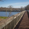 The south landing fishing pier stretches far out into the water. - Chicot State Park