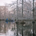 A couple of fishermen try their luck in the lake as the sun sets. - Chicot State Park