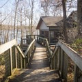 An inviting pathway leading to one of the lakeside cabins.- Chicot State Park Campground + Cabins