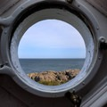 A view from the lighthouse window features the sea and rocky island coastline.- Little River Lighthouse