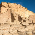 The ruins are located along the side of a canyon wall.- Pueblo Bonito