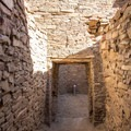 A small hallway leads to a larger room.- Pueblo Bonito
