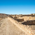 The trail follows along a crumbling wall on the way back to the parking lot.- Pueblo Bonito