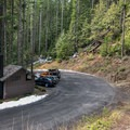 The parking lot is located immediately adjacent to the highway.- Excelsior Pass Snowshoe